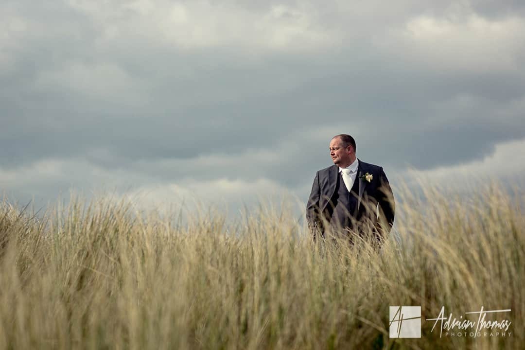 Image of groom during Llanelli wedding on Burry Port beach.