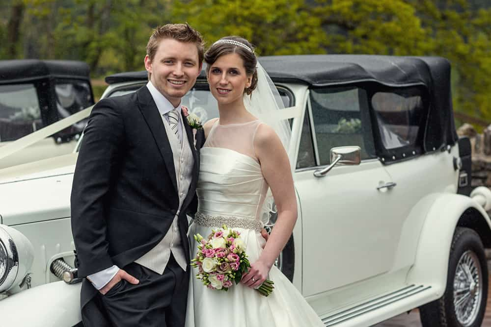 Wedding couple leaning against car