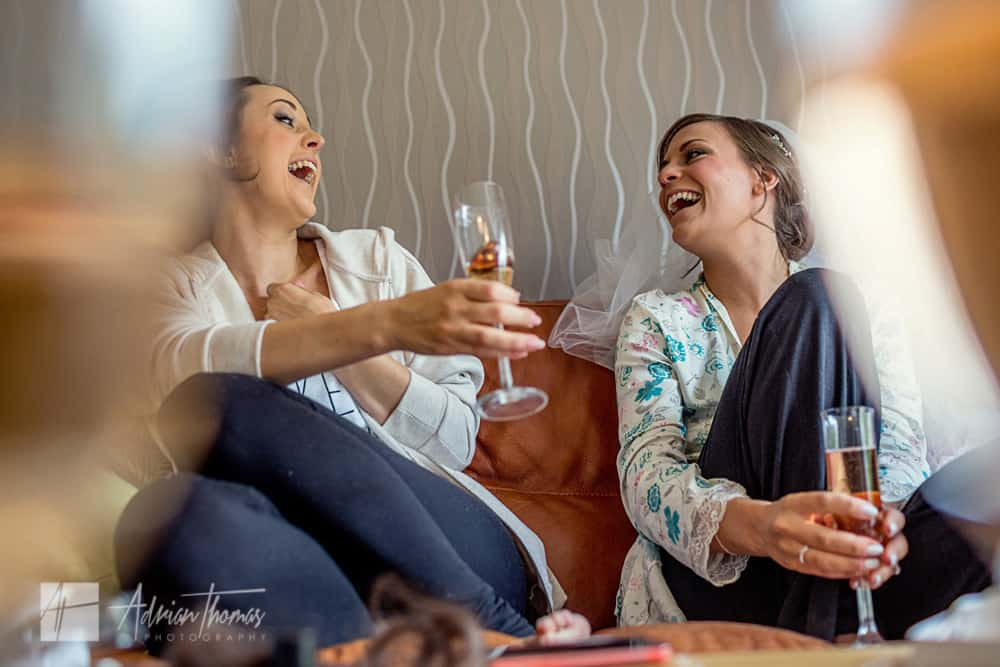 Bride laughing with bridesmaid.