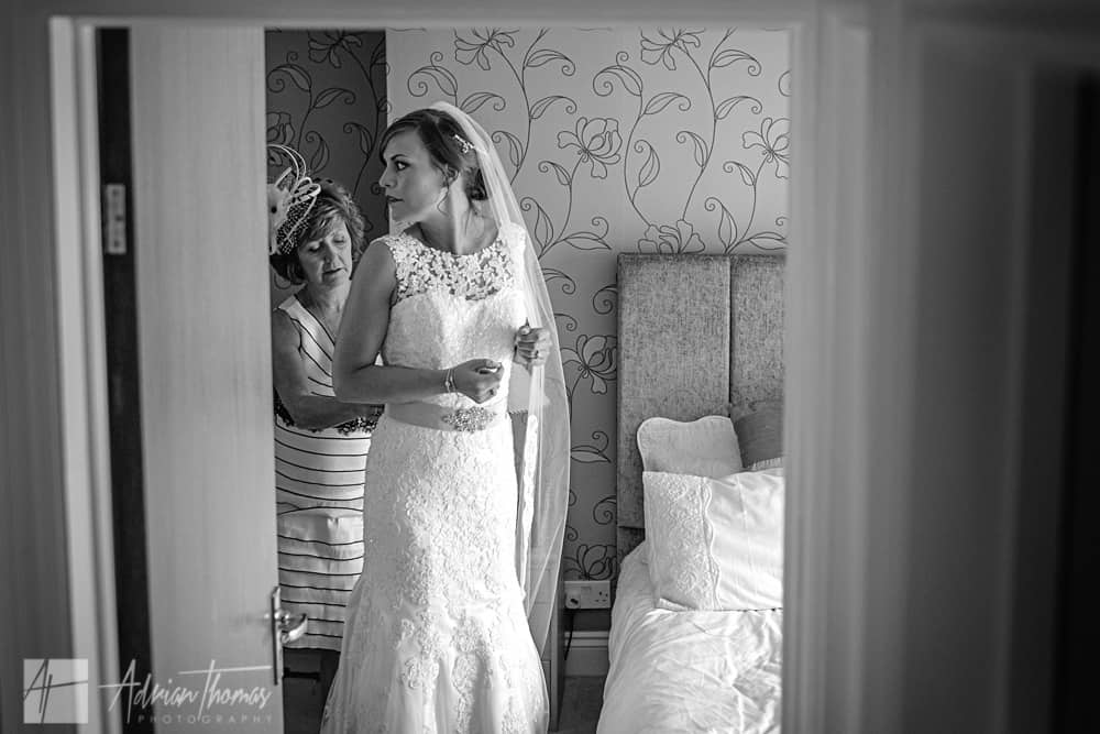 Brides mother helps her daughter get into her wedding dress.