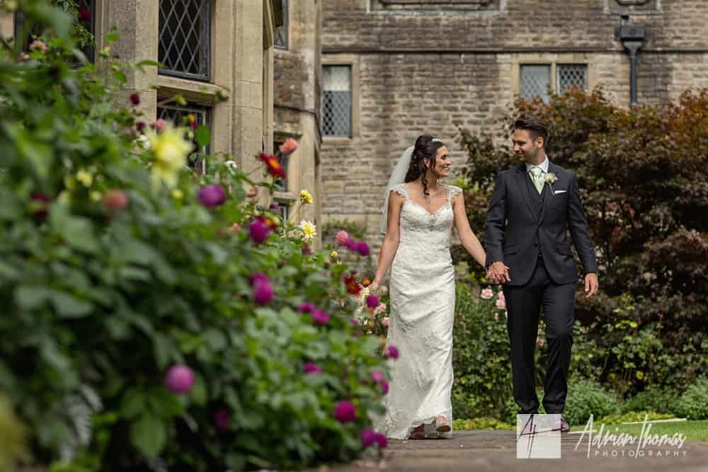 Bride and groom walking romantically around ground of Miskin Manor Hotel wedding venue