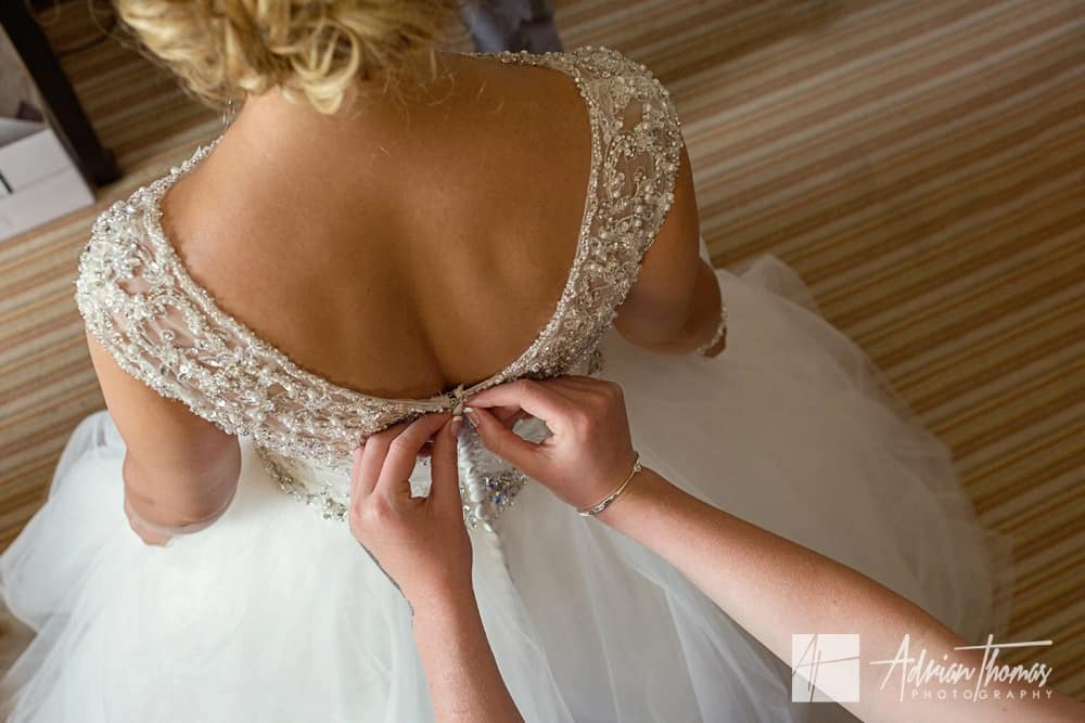 Bride having dress buttoned up