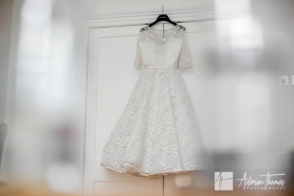 Brides wedding dress hanging on door