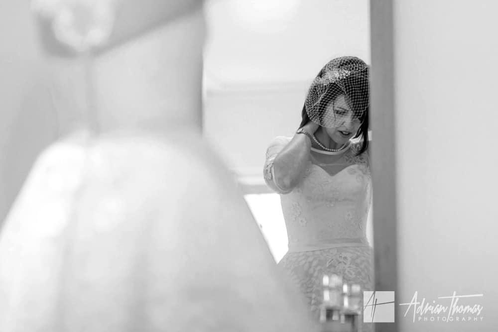 Bride applying her necklace