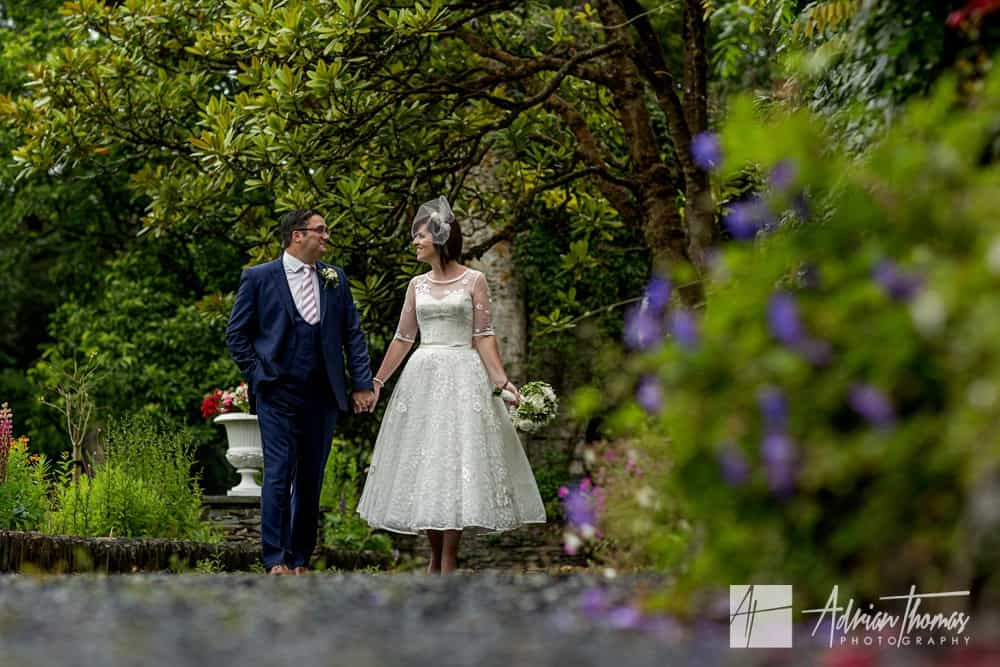 Bride and groom walking around gardens of Castell Deudraeth wedding venue near Portmeirion Village