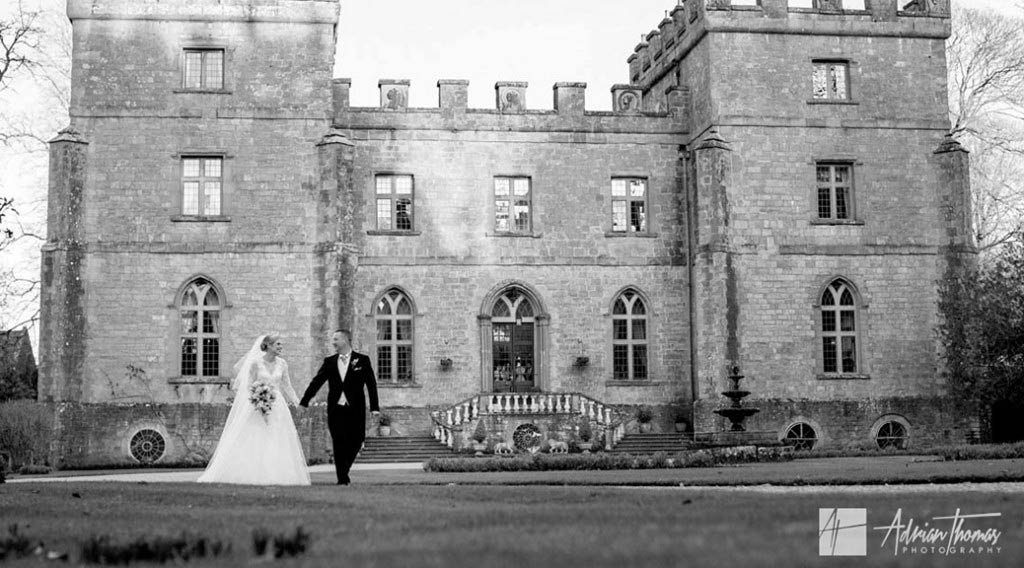 Groom and bride walking around grounds at Clearwell Castle wedding.