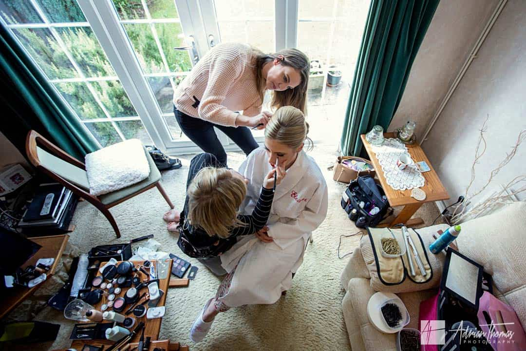 Image of bride having her makeup and hair down at the same time.