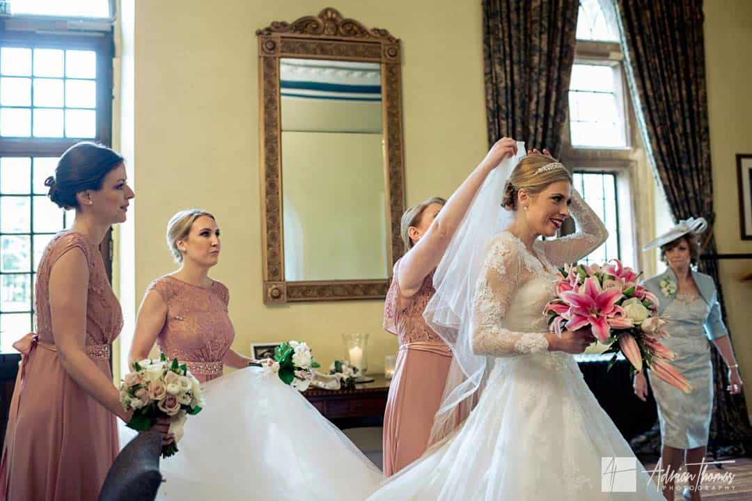 Bridesmaids reapplying wedding veil to brides hair