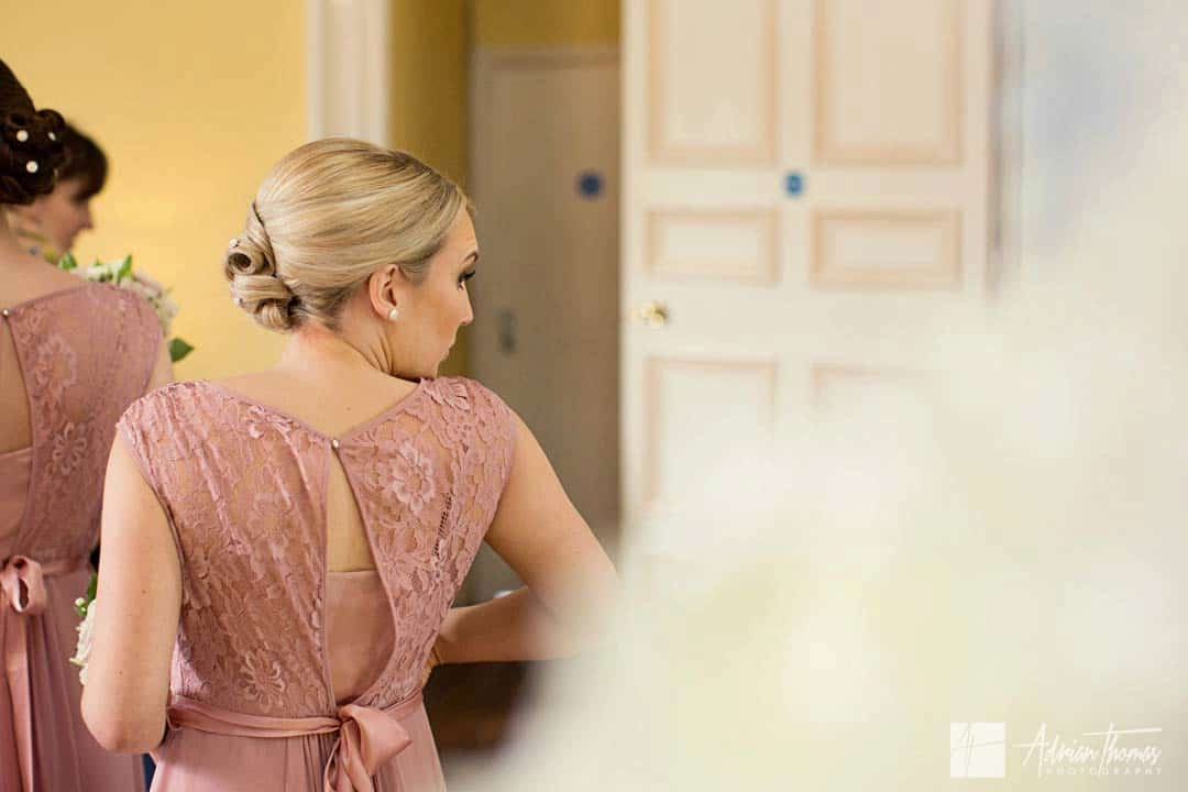 Bridesmaid checking herself in mirror.