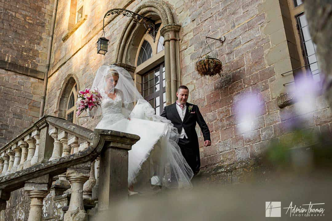 Groom helping bride walk down steps at their Clearwell Castle wedding.