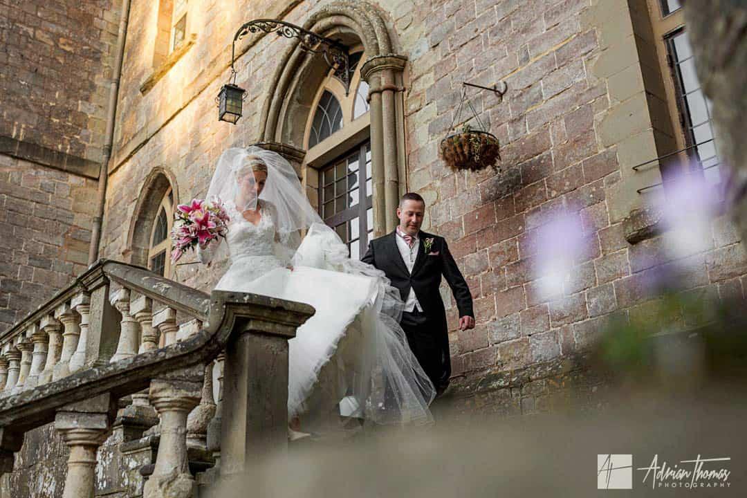 Groom helping bride walk down steps at their Clearwell Castle wedding.