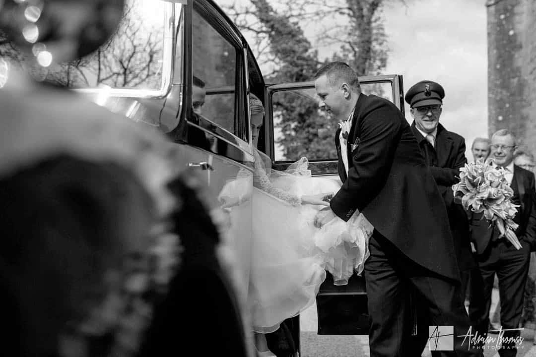 Groom helping bride out of weddig car