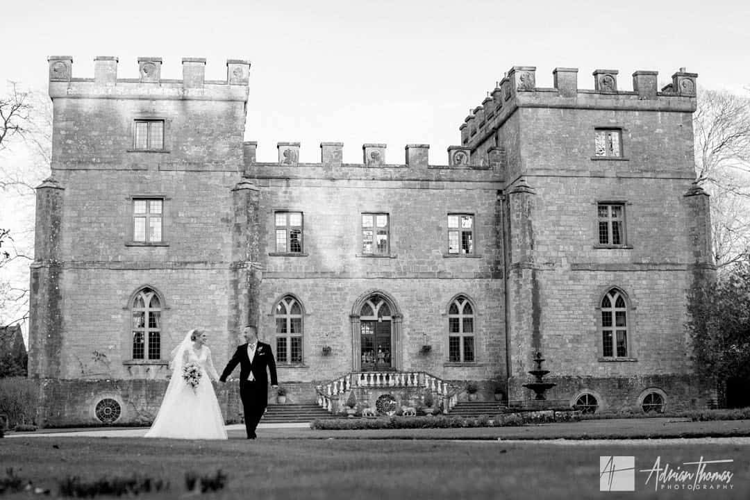 Image of bride and groom walking around grounds during Clearwell Castle wedding.