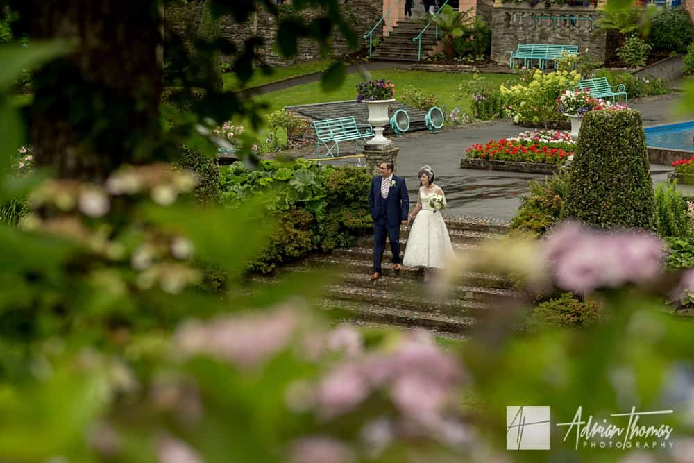 Bride and groom walking through Portmeirion Village Wedding venue.