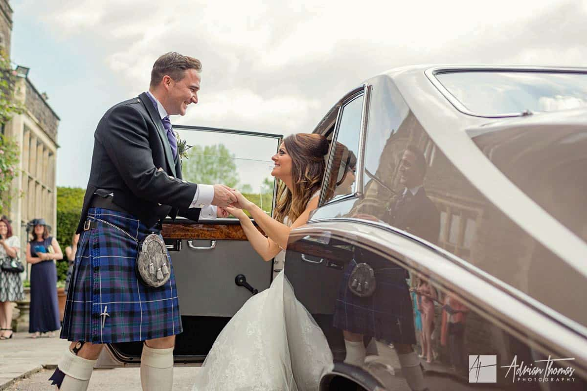 Groom helping he wife out of the car.