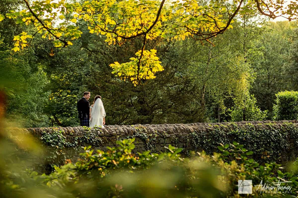 Miskin Manor Wedding venue grounds with bride and groom walking over bridge.