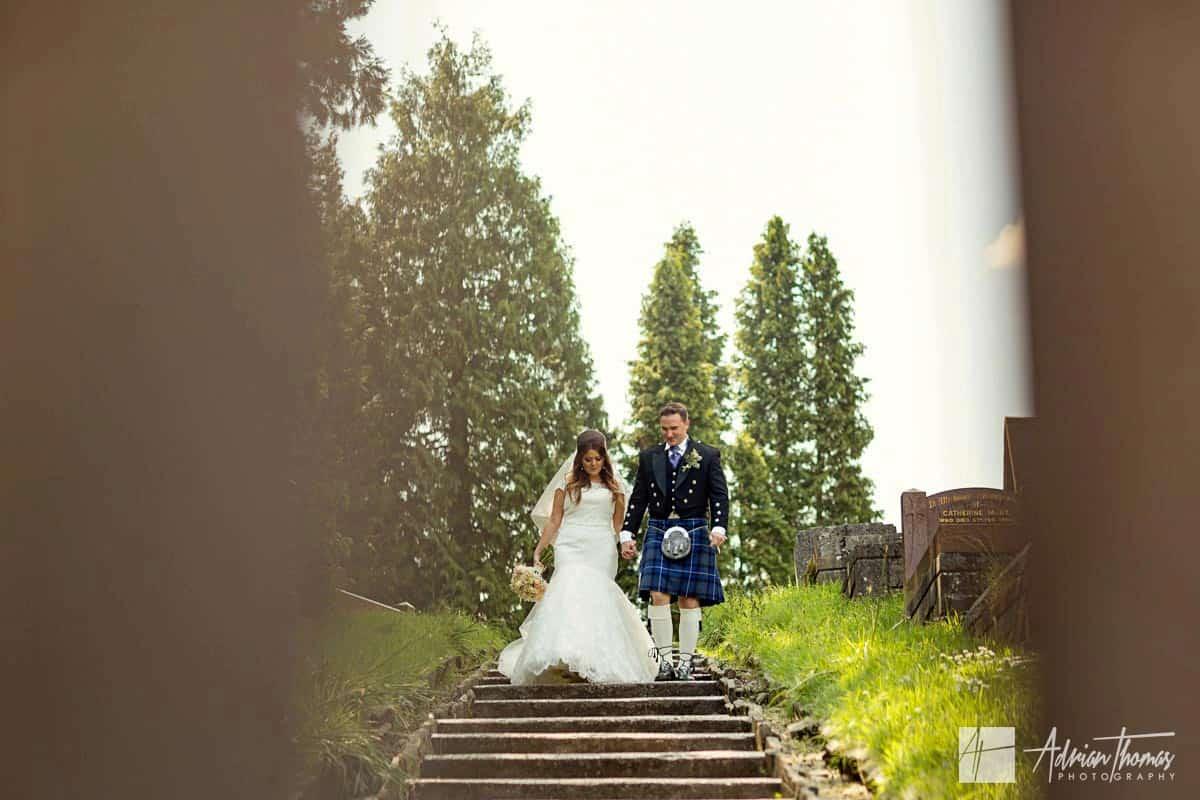 Bride and groom walking down steps at Ystrad Mynach Church.