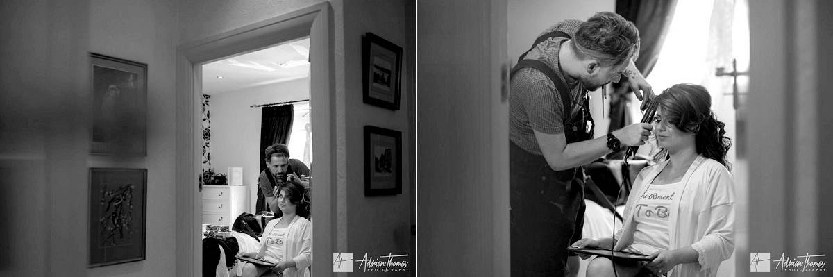 Bride having her hair done in bedroom doorway.