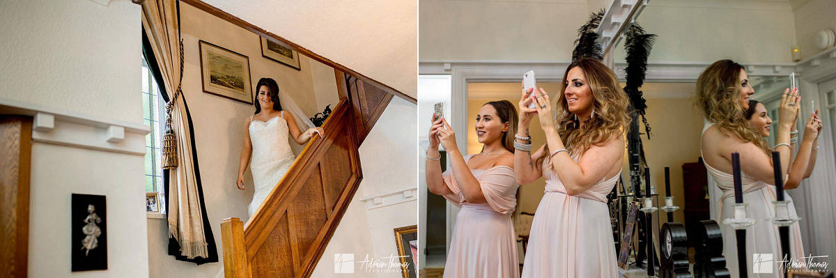 Bridesmaids taking photographs of bride walking down the stairs in her wedding dress.