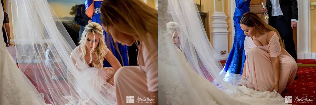 Bridesmaids adjusting brides dress awaiting for groom to arrive.