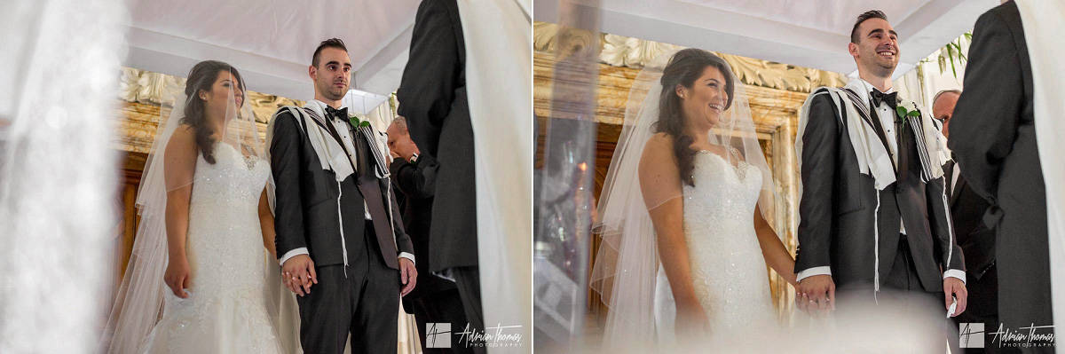 Image of bride and groom laughing during the Jewish wedding ceremony at City Hall Cardiff wedding venue.