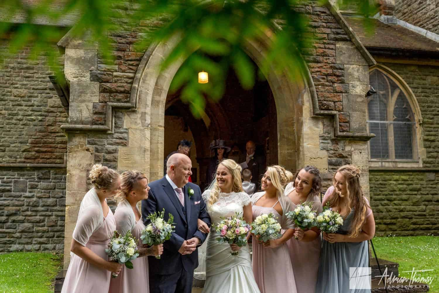 Bride and her dad with bridesmaids smiling before St Martin's Church Caerphilly wedding.