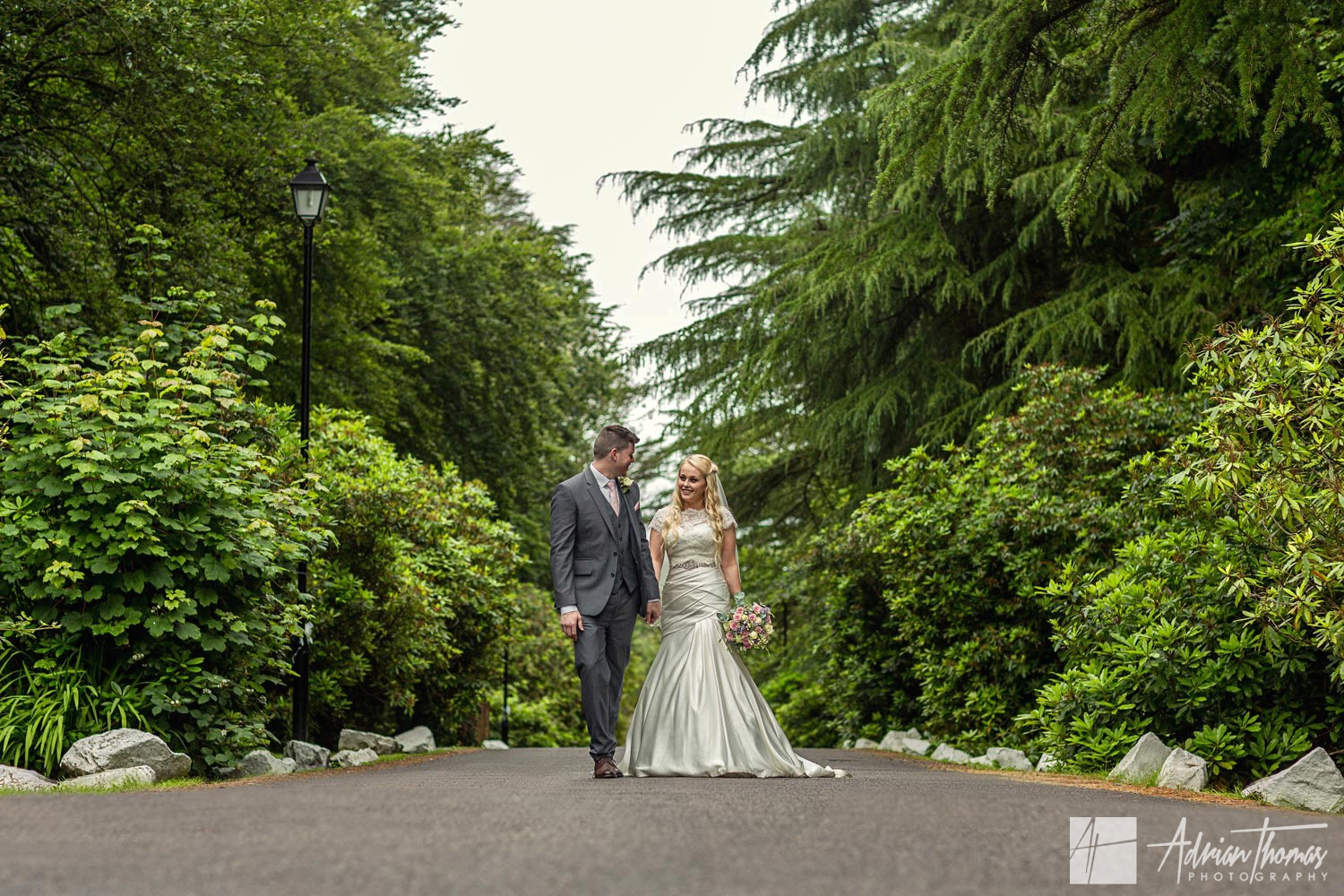 Bride and groom walking hand in hand outside the Maes Manor Hotel wedding venue in Blackwood.