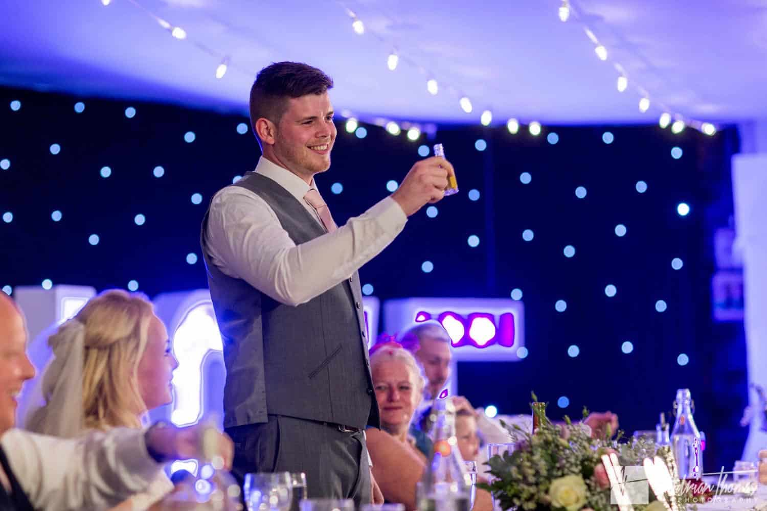 Groom toasting guests and bride.