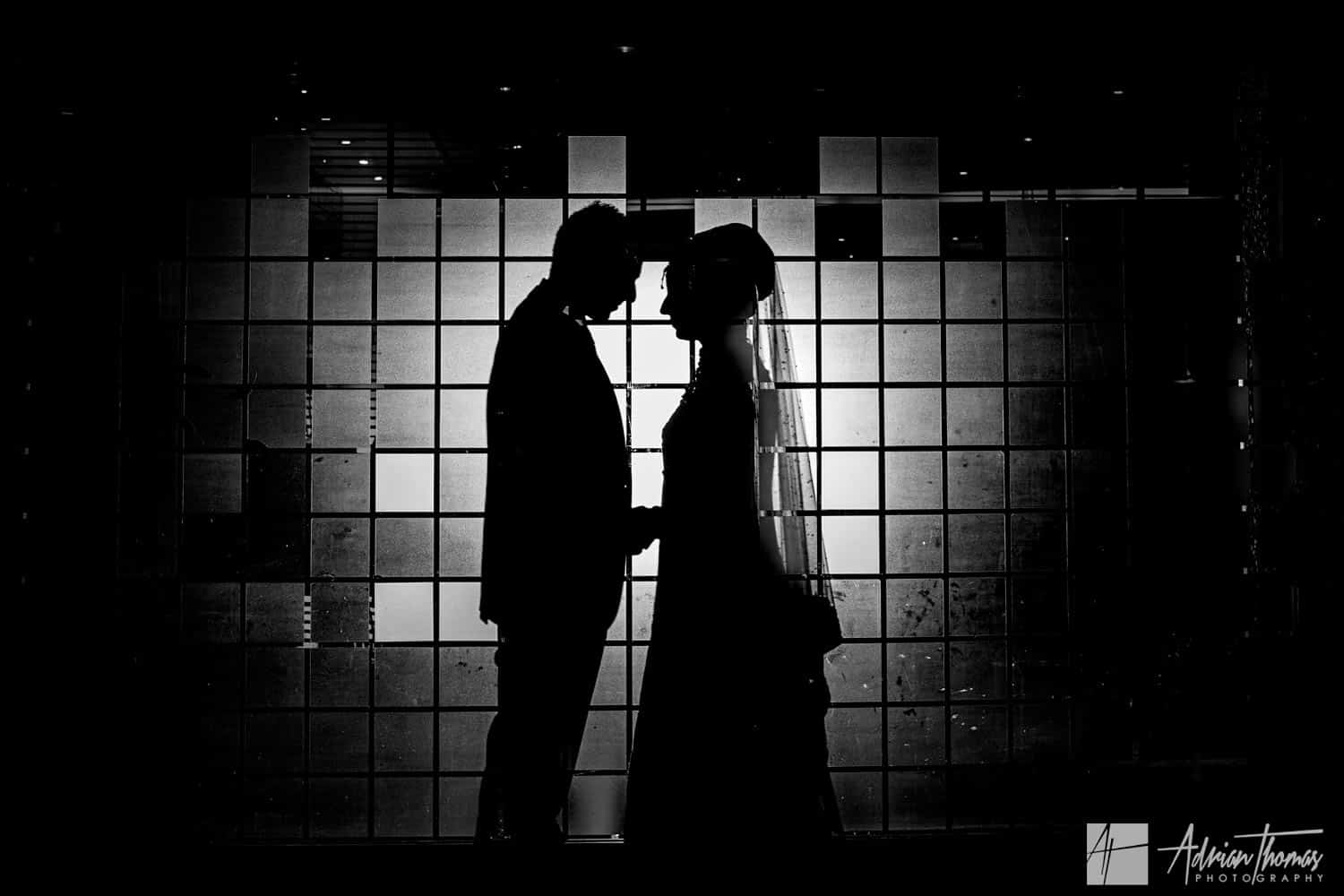 Silhouette image of bride and groom within Sheraton Skyline Asian Wedding