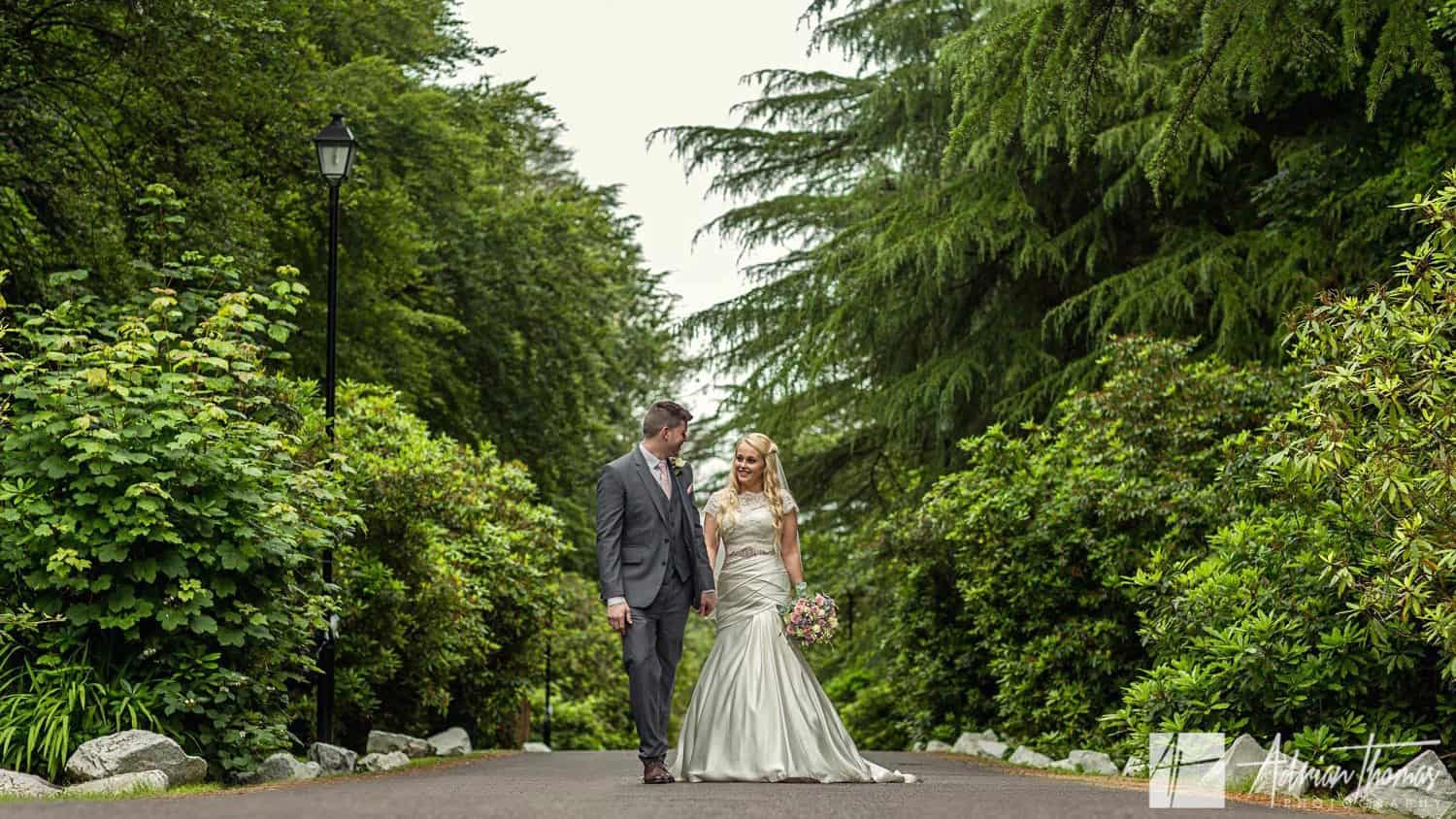 Photograph Bride and groom hand in hand outside the Maes Manor Hotel wedding venue in Blackwood.
